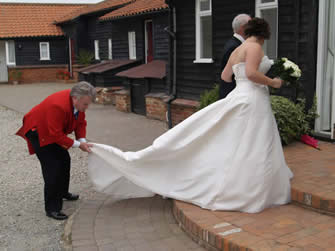 Essex wedding toastmaster assisting bride with her wedding dress